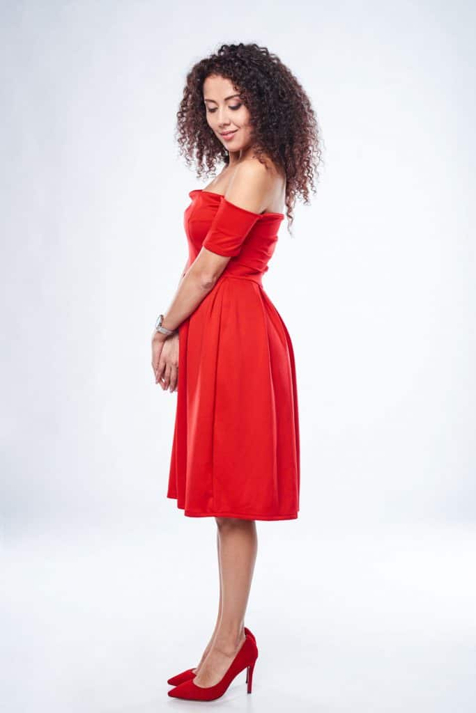 A tall beautiful woman wearing a red dress and red high heeled sofas