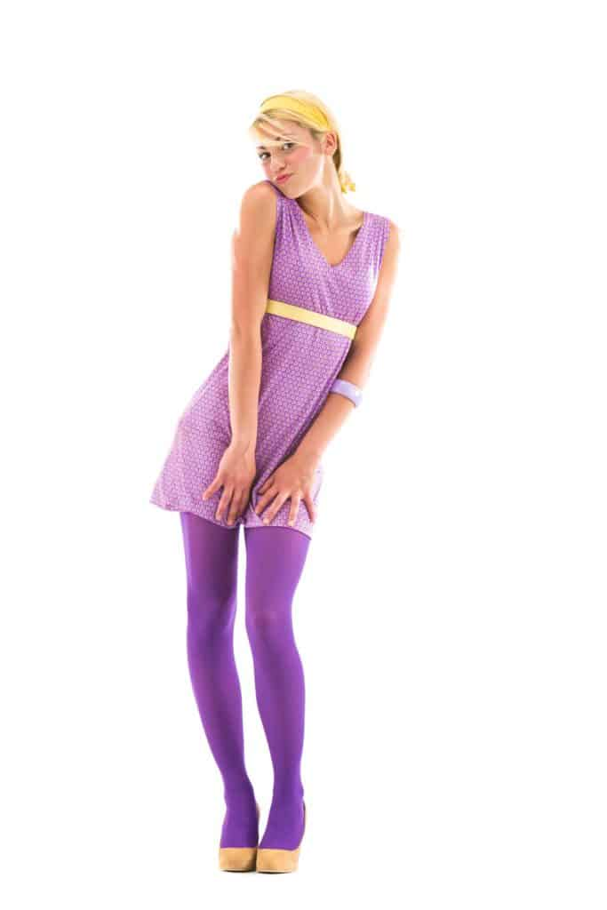 A tall blonde woman a purple dress with purple stocking on a white background