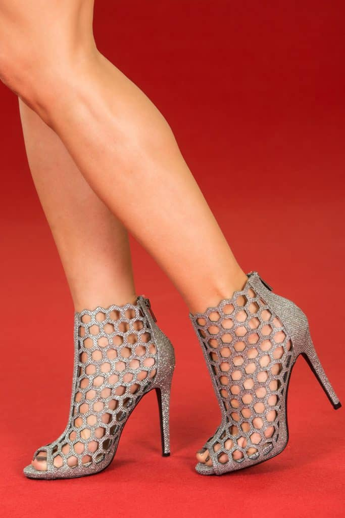 A tall woman wearing high heeled silver shoes