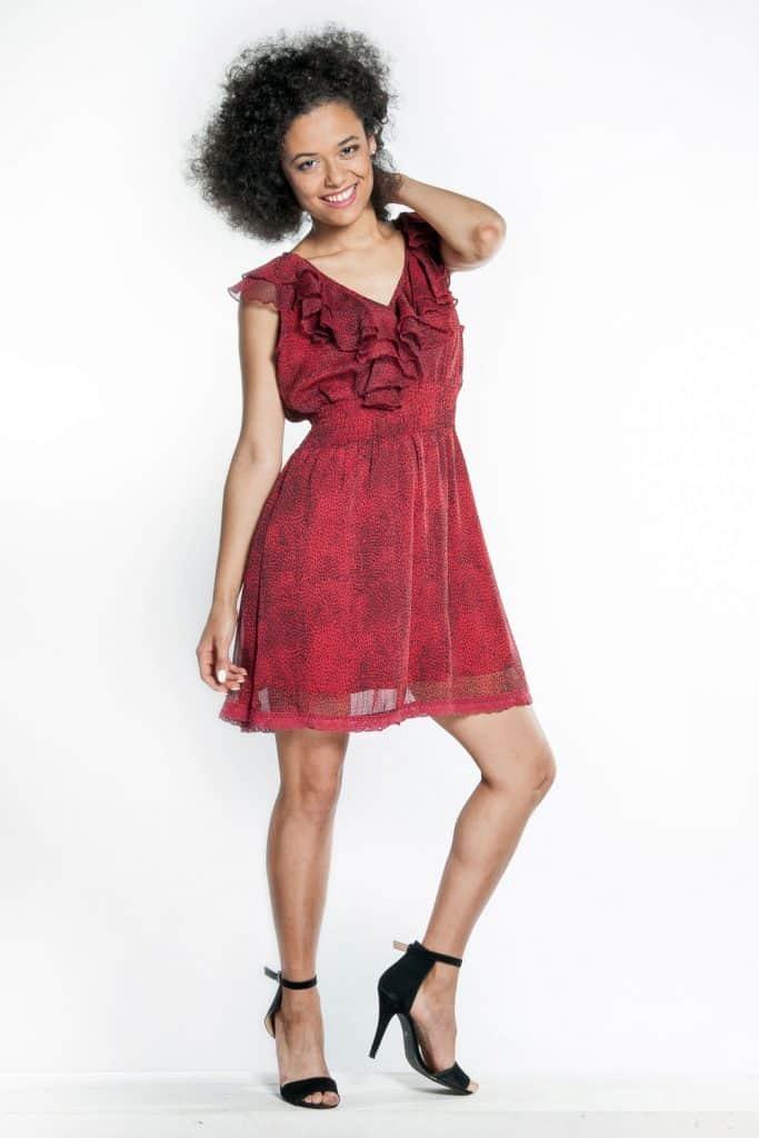A tall woman wearing a short skirt red dress