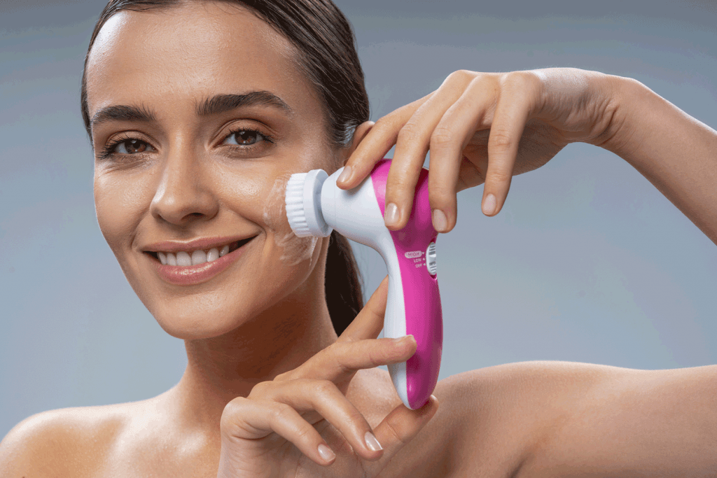 A woman cleaning her face with a face cleanser brush, How To Use A Face Cleanser Brush