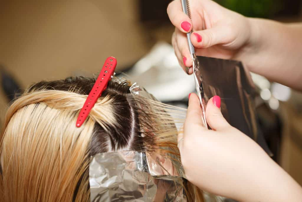 A woman getting her hair dye from a hair artist