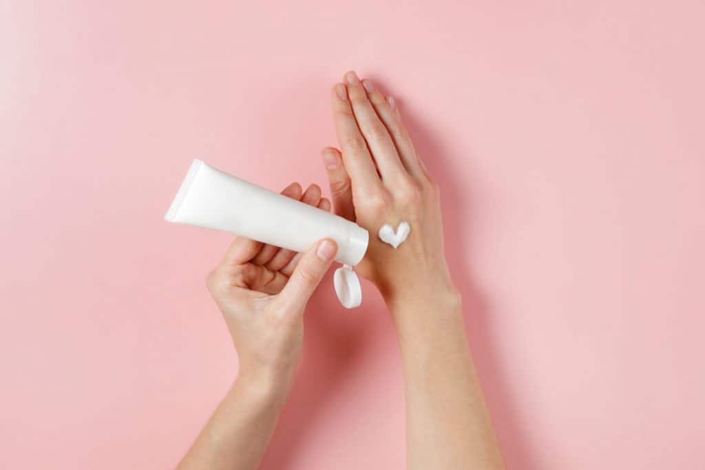 A woman putting a moisturizer on her right hand on a pink background, How Long Does Moisturizer Last (And Can It Expire?)