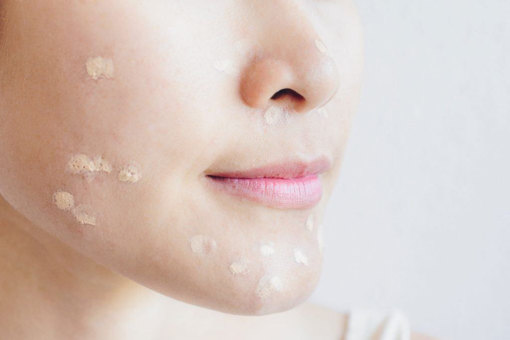 A woman putting face moisturizer on her face, How To Use Tretinoin Cream With Moisturizer