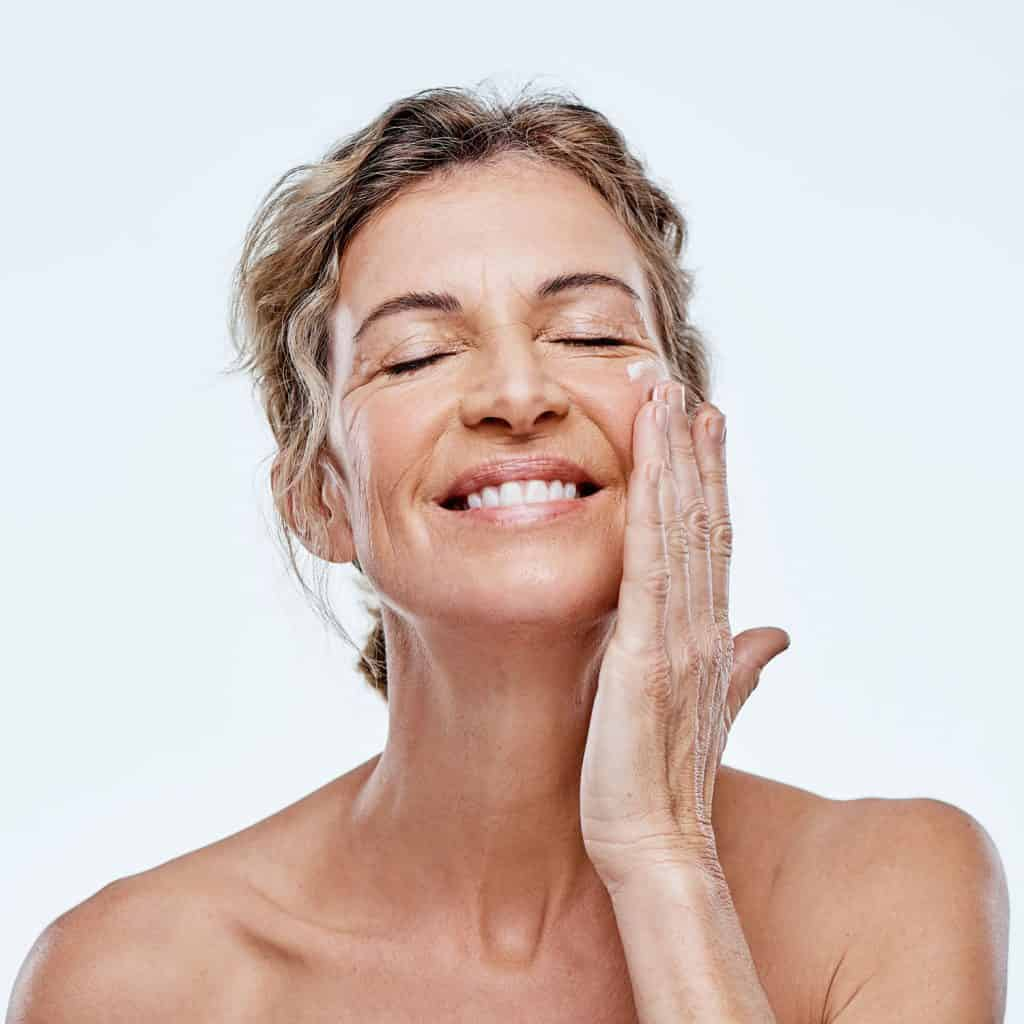 A woman putting moisturizer on her face on a white background