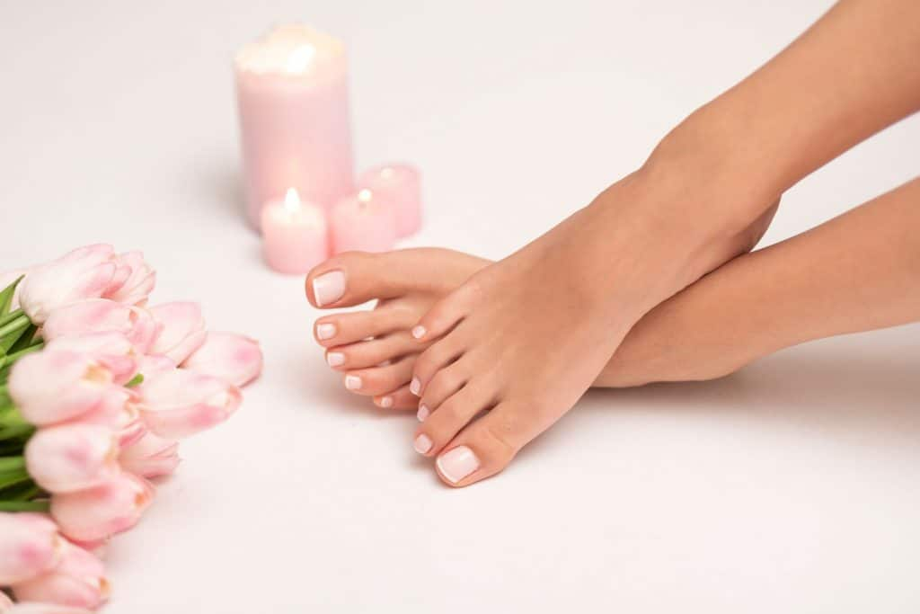 A woman showing her newly gel pedicured nails, How Long Does A Gel Pedicure Last? [And How Often To Get One!]