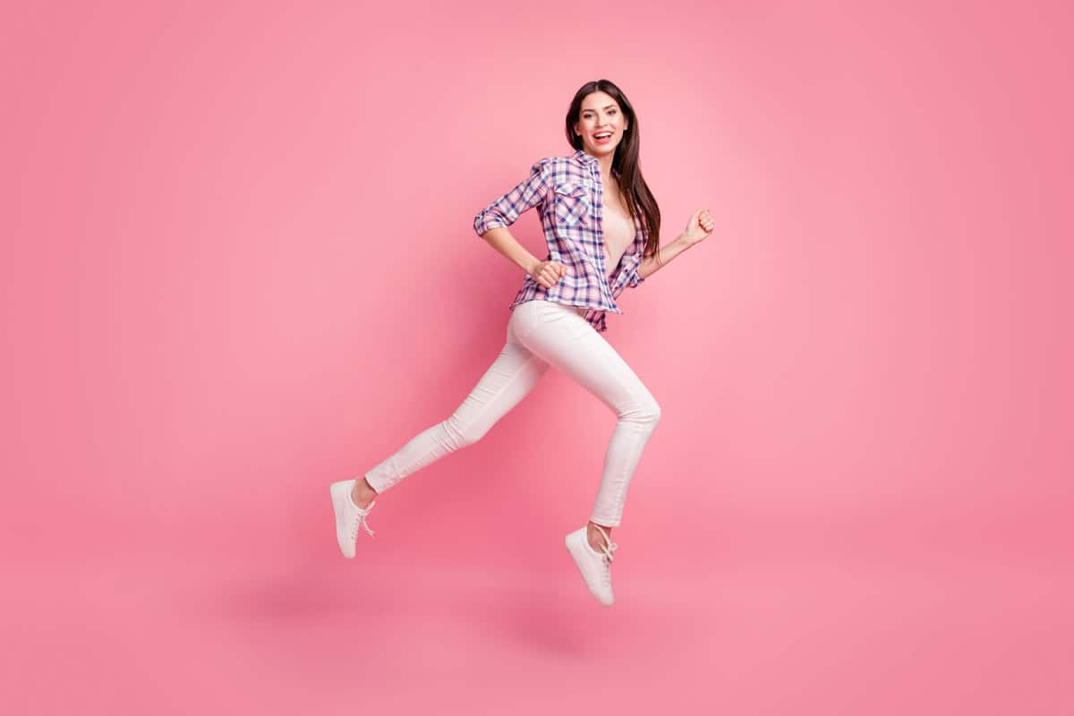 A woman wearing a checkered shirt pink shirt and white jeans with matching white shoes, What Color Shoes Can You Wear With White Jeans?