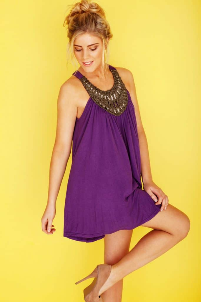 A woman wearing a flowy purple dress statement necklace and brown sandals on a yellow background