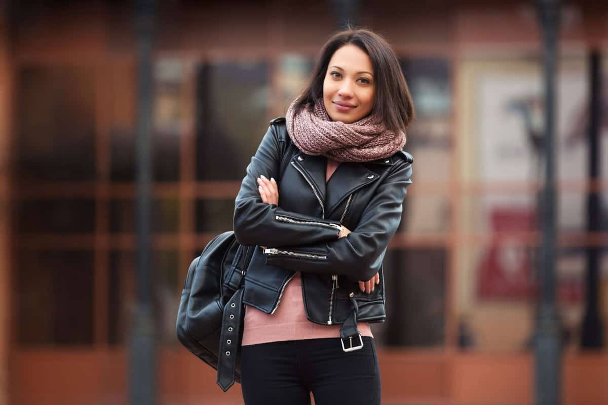 A woman wearing a leather jacket and scarf in the cold New York weather, Should A Leather Jacket Be Tight Or Loose?