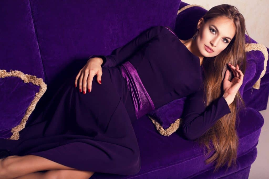 A woman wearing a long purple dress while lying on the purple couch