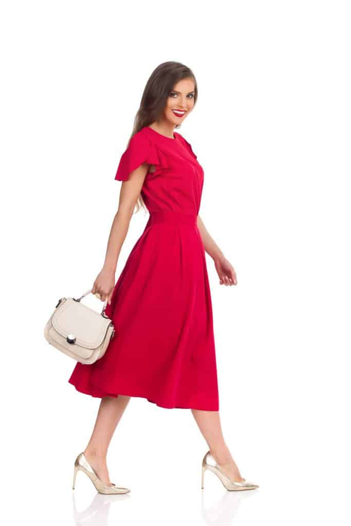 A woman wearing a long red dress while holding a clutch bag on a white background