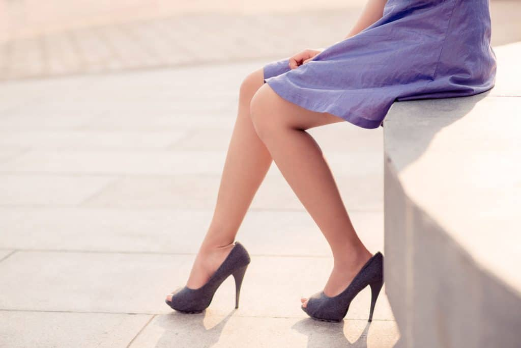 A woman wearing a purple dress and purple high heeled sandal sitting on the public fountain