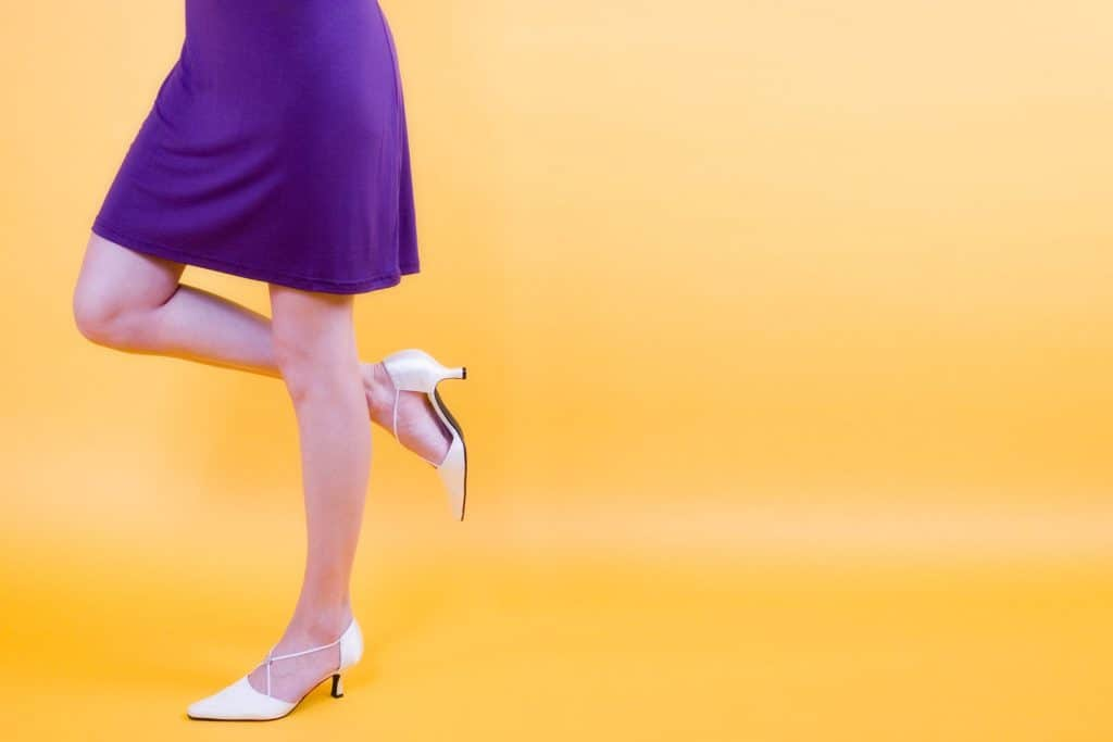 A woman wearing a purple dress and white shoes on a yellow background