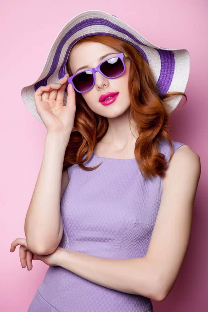 A woman wearing a purple dress, purple sunglasses, and a purple sunhat on a purple background