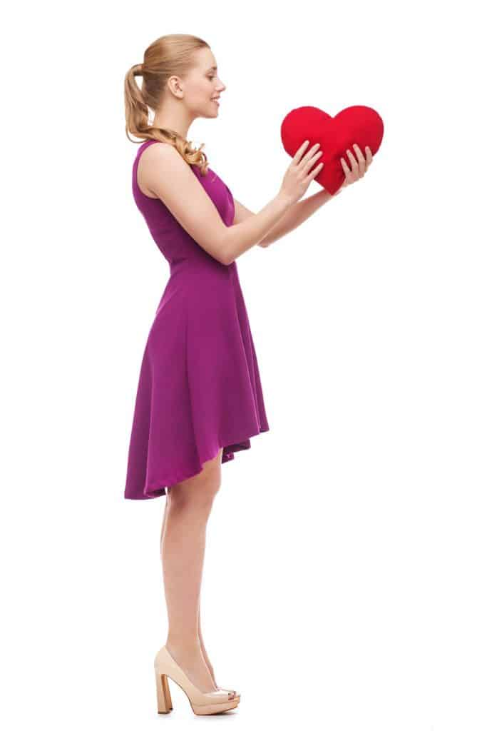 A woman wearing a purple dress while holding a heart on a white background