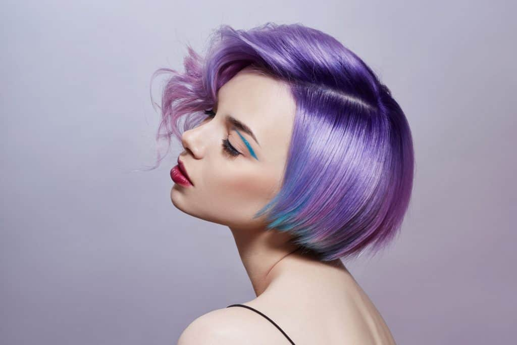 A woman with purple dyed hair on a purple background