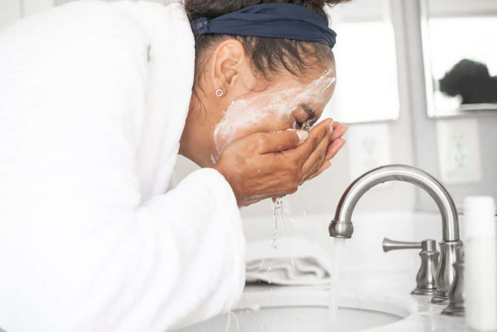 A young woman washing her face int he bathroom
