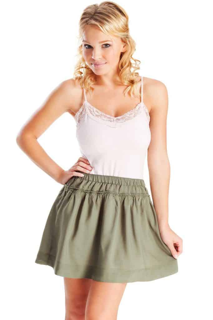 An attractive young blonde woman posing in a green skirt and pink tank top