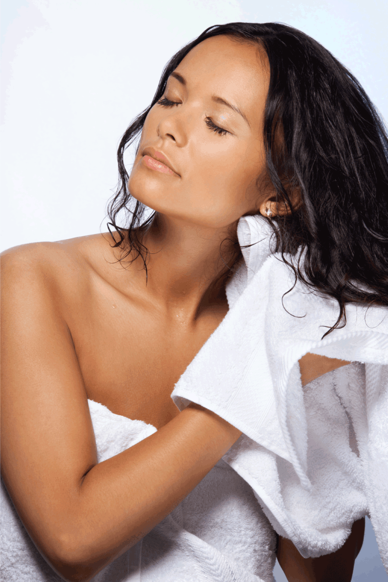 Asian woman wiping wet hairs after bathroom with blanket with relaxed expression