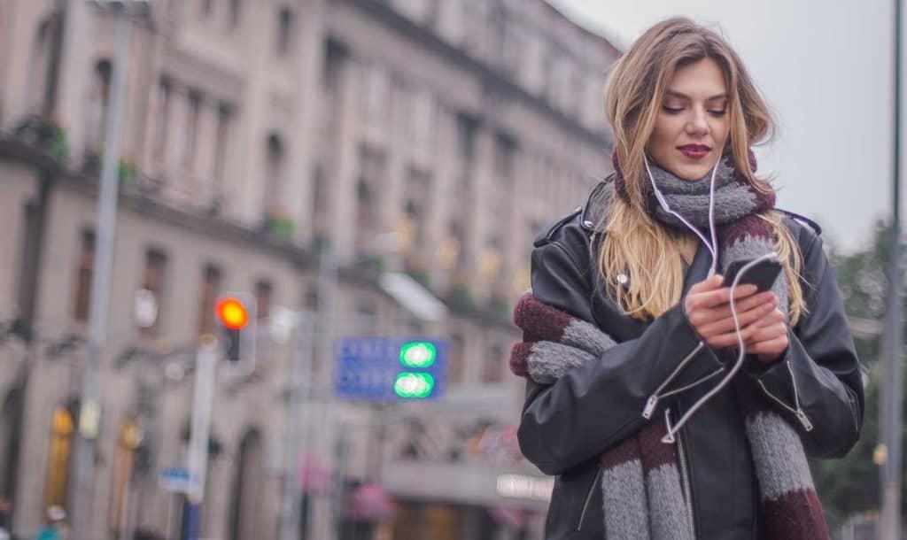 Beautiful blonde woman dressed in biker jacket having a walk through the city streets