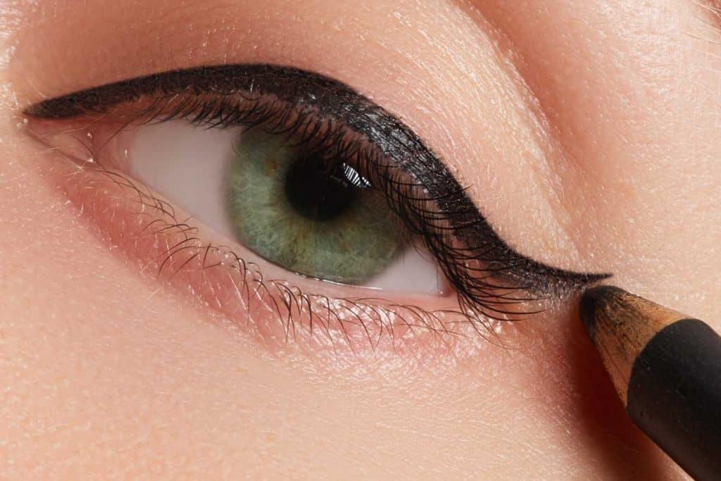 Beautiful model applying eyeliner on top lid, How To Put Eyeliner On Top Lid In 4 Easy Steps