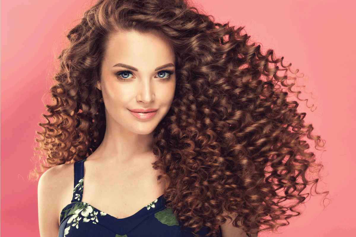 Beautiful model girl with long curly hair . Care products ,hair coloring