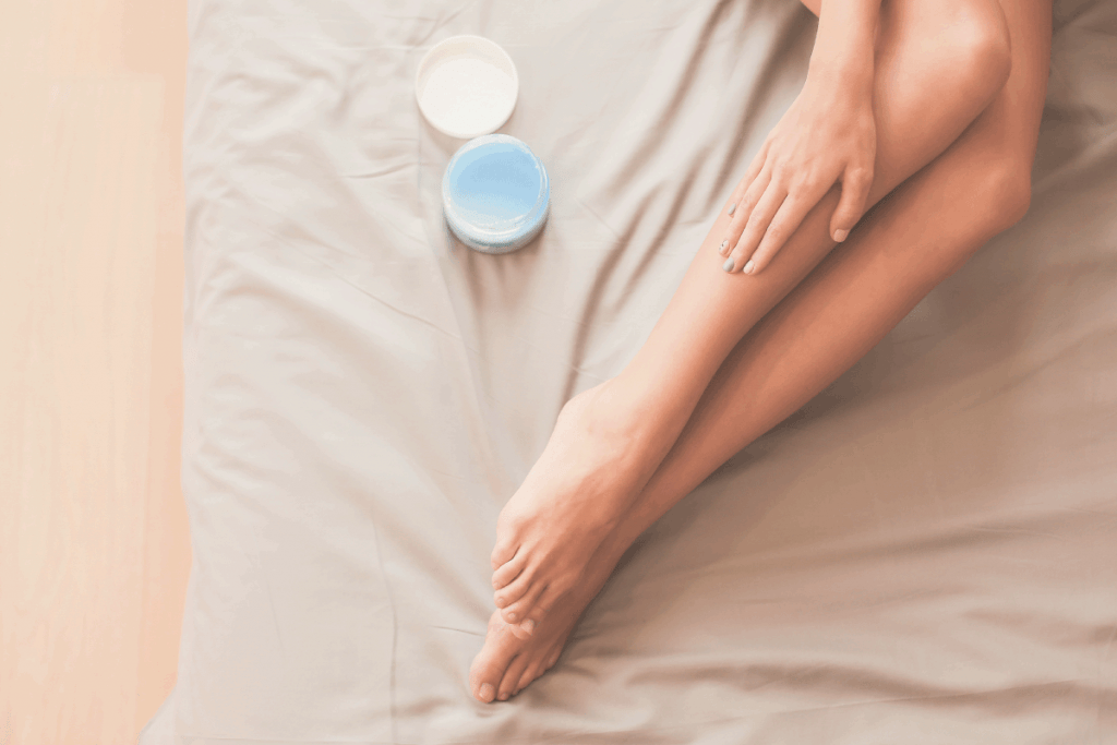 Beautiful woman sitting on bed and applying cream on legs. Can You Moisturize Too Much