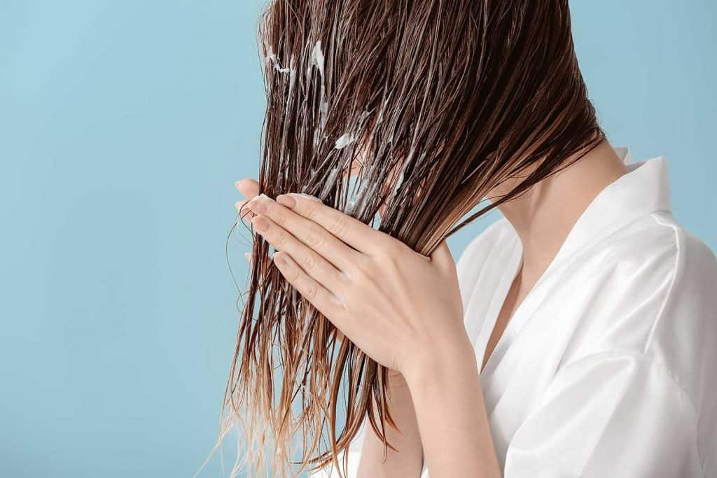 Beautiful young woman applying mousse on her hair after washing