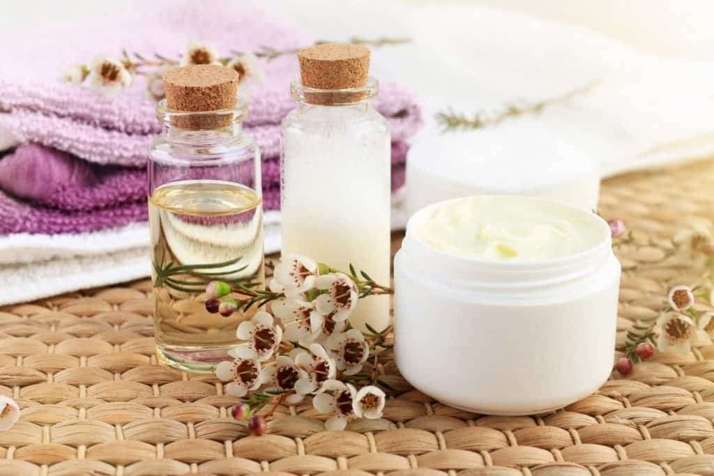 Bottle of essential oil with flowers, jar of facial moisturizer, towels, sunlight