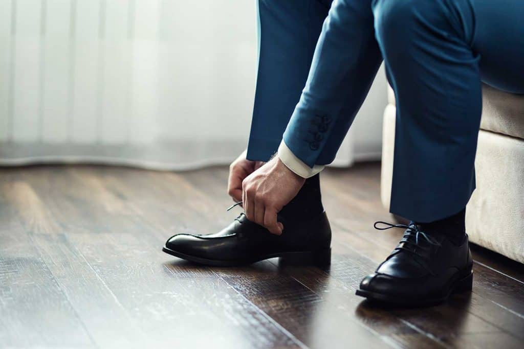 Businessman in suit tying his black leather shoes