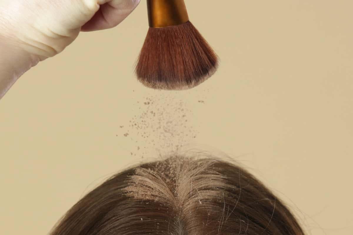 Close up view at woman applaying natural dry shampoo on hair roots
