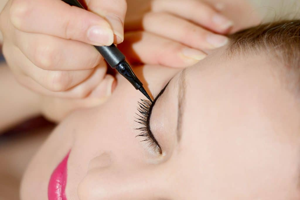 Extreme Close-Up of woman applying eyeliner, Can You Use Liquid Eyeliner On Your Waterline?