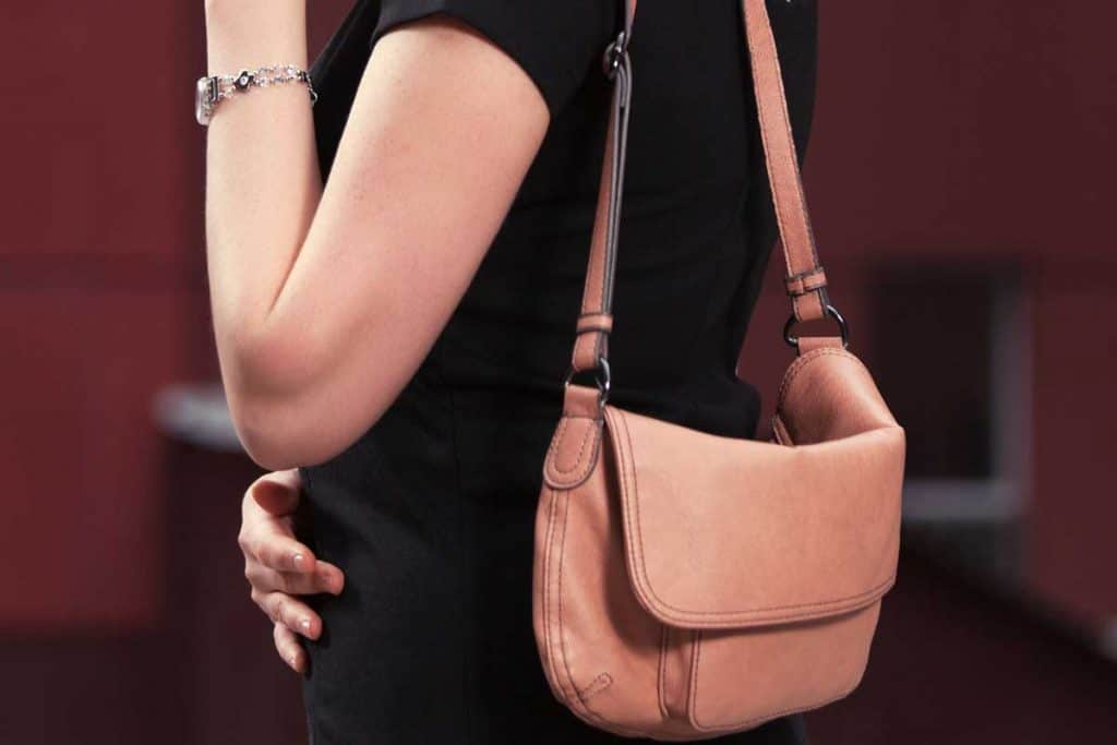 Fashion blond woman in black dress walking on city street, How To Wear A Shoulder Bag [4 Incredible Ways]