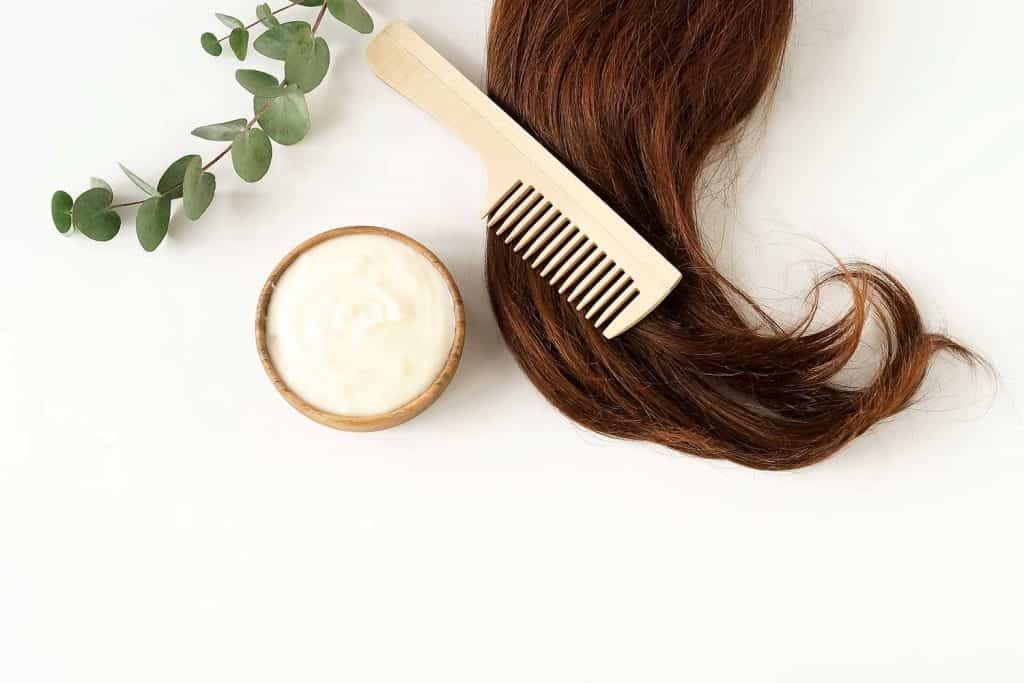 Female hair, hair mask and bamboo comb on white background