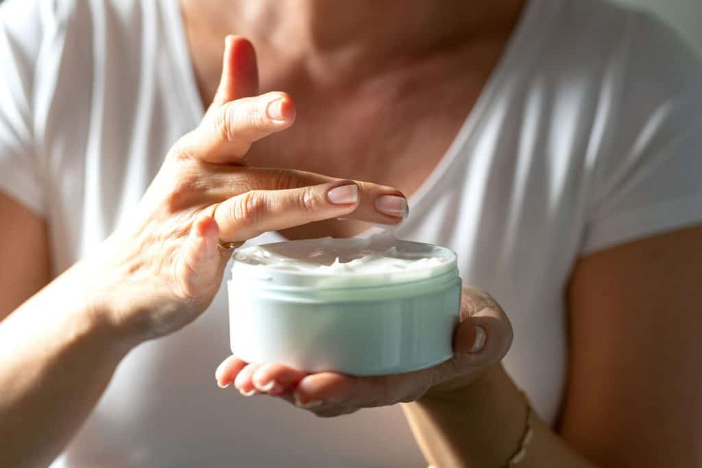 Female hands holding a jar of facial cream and taking a little bit with her finger for application, Should You Wash Off Moisturizer Or Leave It On Your Face?