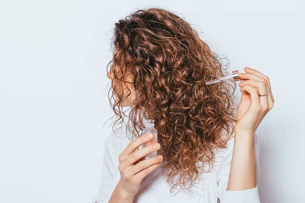 Female's hands using cosmetic serum to prevent split ends