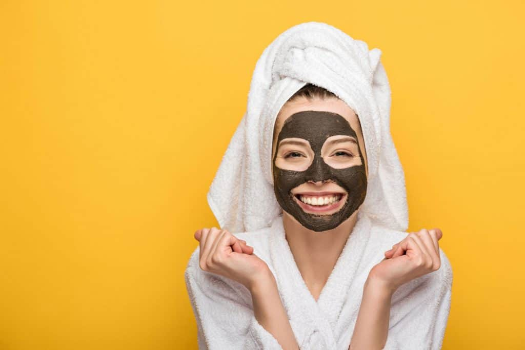 Happy girl with facial clay mask and towel on head holding clenched fists and looking at camera isolated on yellow