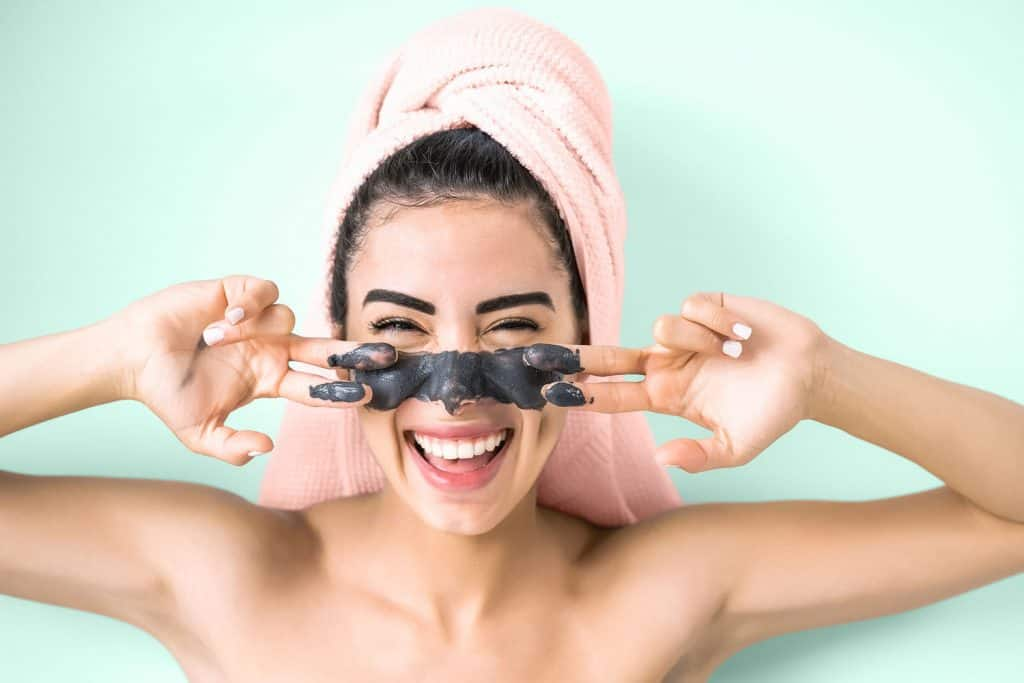 Happy smiling girl applying facial charcoal mask portrait - Young woman having skin care cleanser spa day, Do Clay Masks Absorb Oil And Do They Clean Pores?