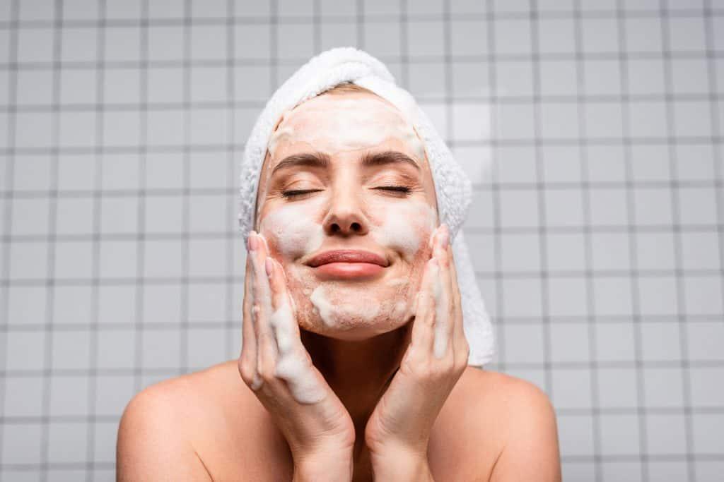 Happy woman with closed eyes applying foam cleanser in bathroom