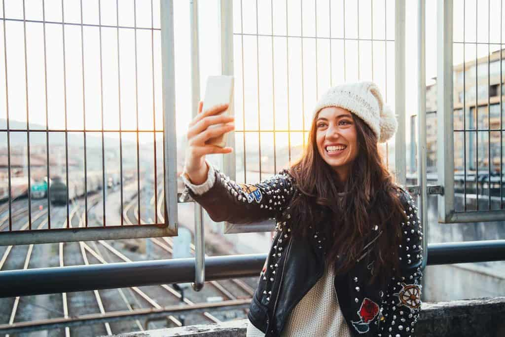 Happy young woman in leather jacket taking a selfie with her phone over the train station at sunset