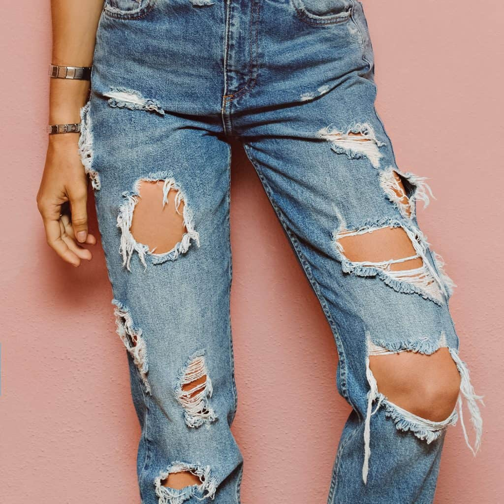 Lady in fashionable ripped jeans stands in pink wall