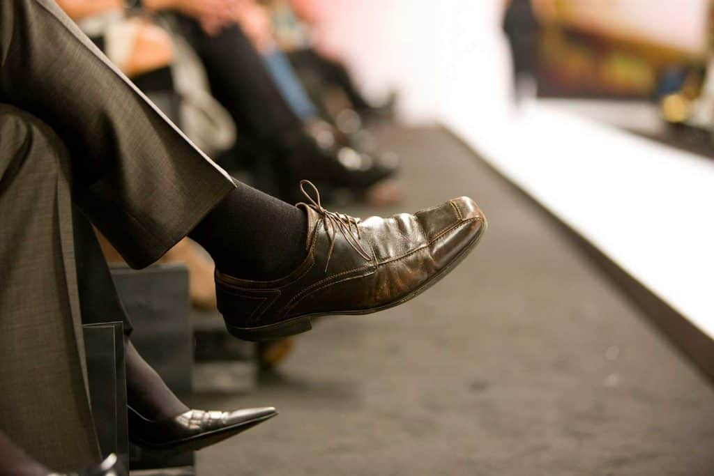 Man in suit and leather shoes watching beside fashion runway
