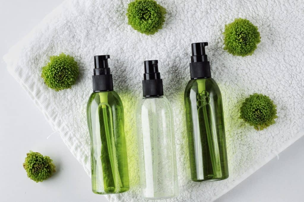 Organic skincare products on minimalistic SPA background with flowers