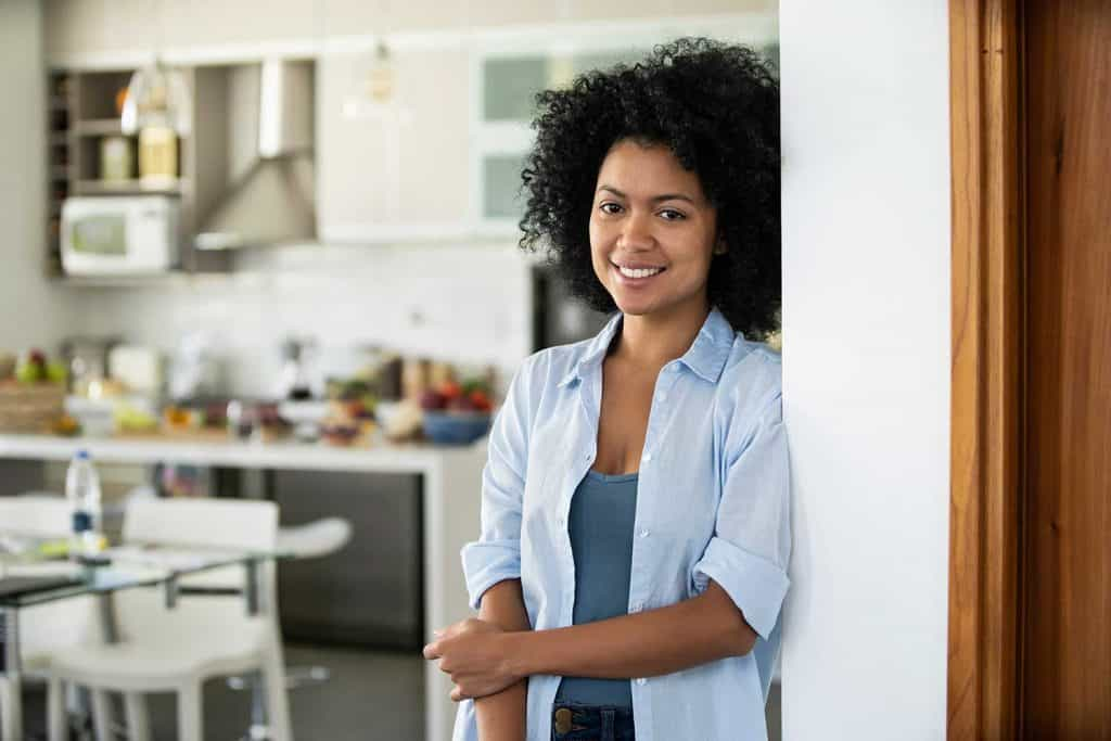 Portrait of smiling young woman standing in kitchen