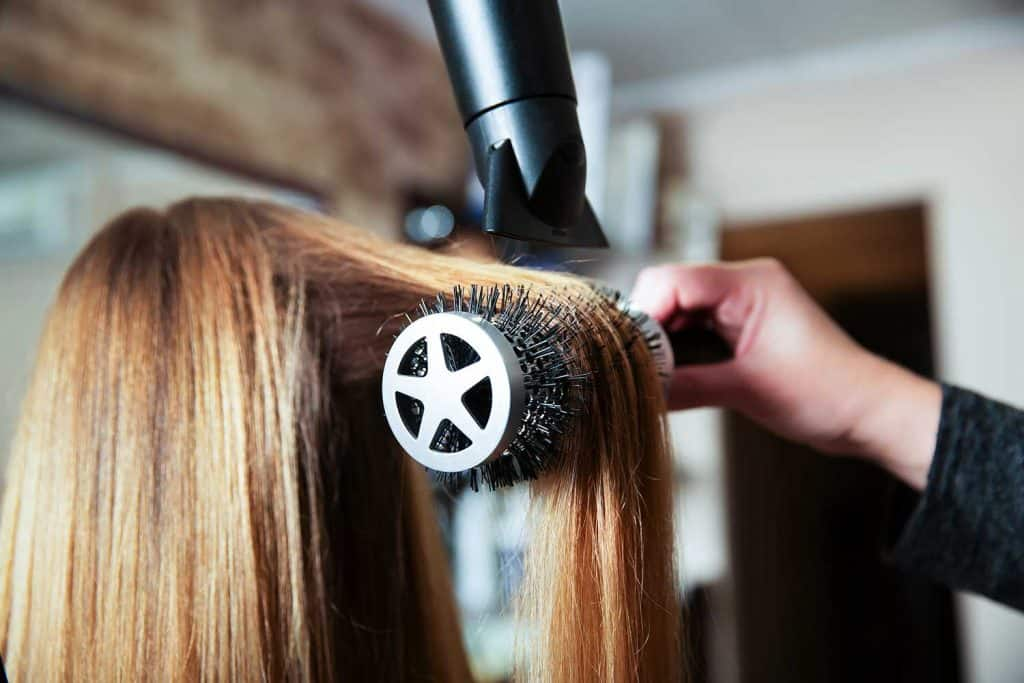Professional woman hairdresser making hairstyle using hair dryer for young female in beauty salon