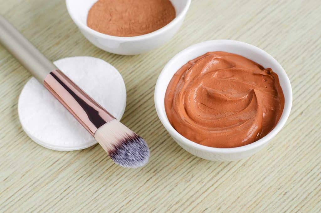 Small white bowl with red cosmetic clay mask