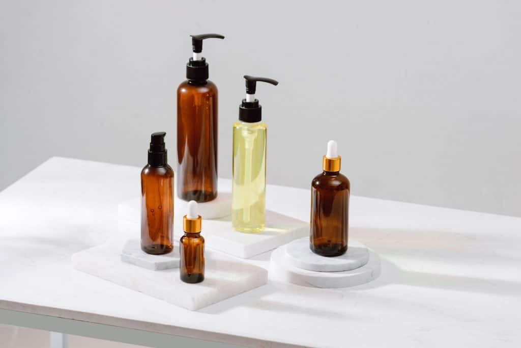Spa cosmetics in brown glass bottles on gray concrete table