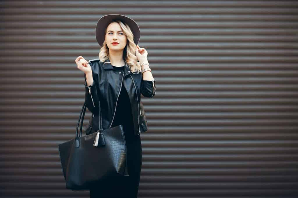 Street portrait of glamour sensual young stylish lady wearing trendy fall outfit. Blonde woman in black hat and leather jacket and bag