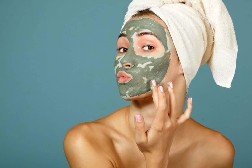 Teen girl applying facial clay mask