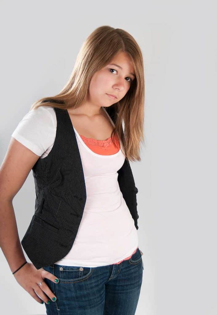Teenage girl wearing jeans, flip flops, white t-shirt and vest isolated on white